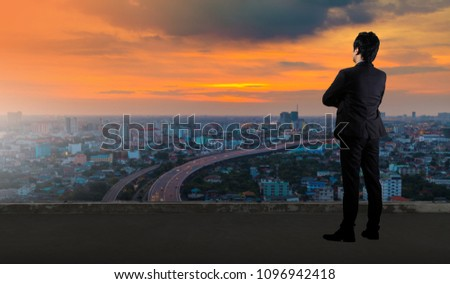Businessman standing on roof and looking at Cityscape skyline night light #1096942418