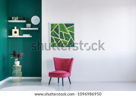 Modern white and green interior with red armchair, shelves, plant and painting on the wall #1096986950