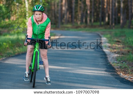 Girl in sports uniform on a bicycle in the park. Sport activities and active way of life. #1097007098