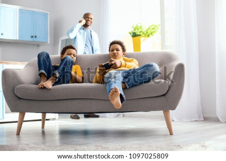 Peaceful pastime. Charming little boys sitting on the sofa and playing video game while their father having a phone conversation in the background #1097025809