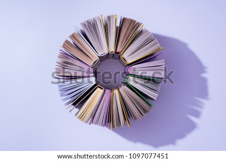 top view of stack of books in circle on violet tabletop