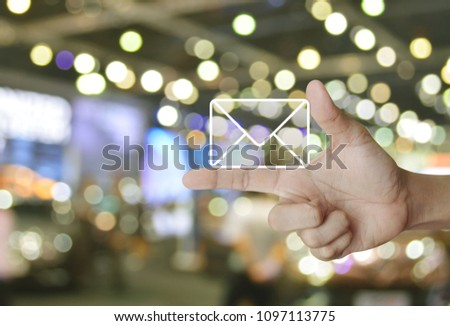 Mail icon on finger over blur light and shadow of shopping mall, Contact us concept #1097113775