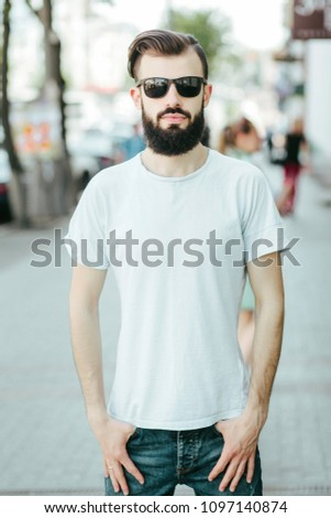 A young stylish man with a beard in a white T-shirt and glasses. Street photo #1097140874