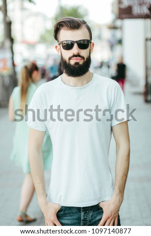 A young stylish man with a beard in a white T-shirt and glasses. Street photo #1097140877