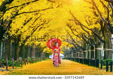 Beautiful girl wearing japanese traditional kimono at row of yellow ginkgo tree in autumn. Autumn park in Tokyo, Japan. #1097142689