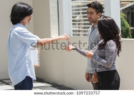 portrait of asian young house seller giving the key to the new owner #1097233757