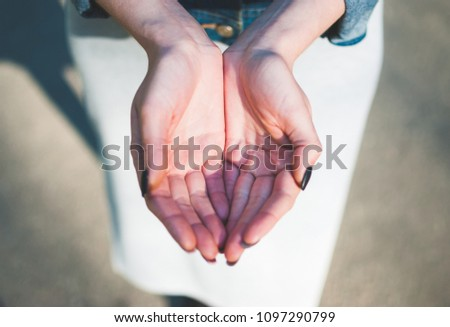 Girl making a cupped palms gesture against sunny asphalt background. Open palms. Close-up. #1097290799