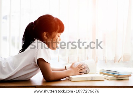 Cute little girl reading a book in library ,lifestyle education Knowledge Concept #1097296676