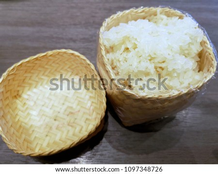 Hot sticky rice in wood basket on black table #1097348726