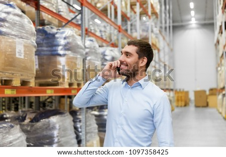 wholesale, logistic business and people concept - smiling businessman calling on smartphone at warehouse #1097358425