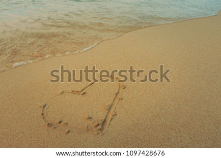 Alone heart on the sand. Beautiful background beach with alone heart in summer. Royalty high-quality free stock photo image of shape heart draw on the sandy beach and wave