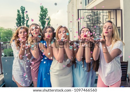 Girls Party. Beautiful Women Friends on the balcony Having Fun At Bachelorette Party. They are blowing confetti from hands. Selective focus #1097466560