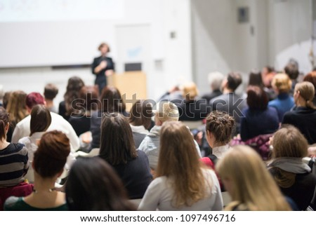 Female speaker giving presentation in lecture hall at university workshop. Audience in conference hall. Rear view of unrecognized participant in audience. Scientific conference event. #1097496716