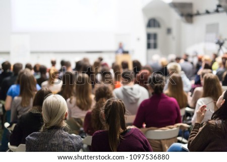 Female speaker giving presentation in lecture hall at university workshop. Audience in conference hall. Rear view of unrecognized participant in audience. Scientific conference event. #1097536880