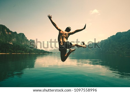 Man jumping with joy by a lake Royalty-Free Stock Photo #1097558996