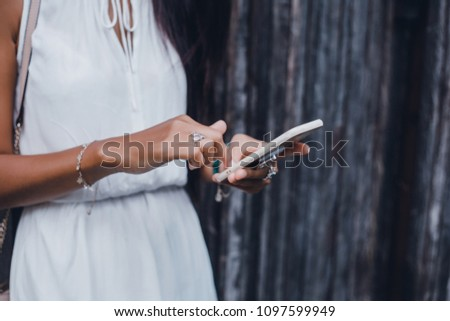 Close up of women's hands holding cell telephone with blank copy space scree for your advertising text message or promotional content, hipster girl watching video on mobile phone during coffee break #1097599949