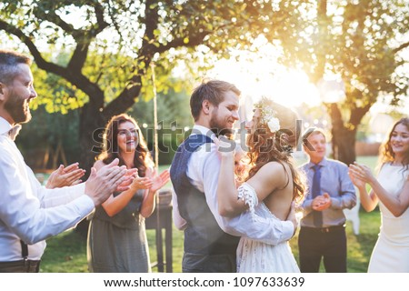 Bride and groom dancing at wedding reception outside in the backyard. #1097633639