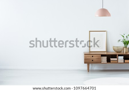 Retro pink ceiling lamp above a wooden sideboard in a modern living room interior with an empty white wall and copy space. Place for your sofa #1097664701