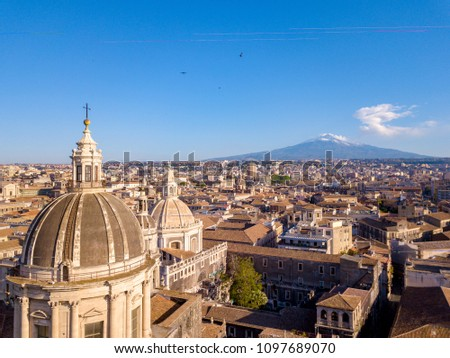 Aerial view of the Cathedral of Sant'Agata in the middle of Catania with Etna volcano on the background #1097689070