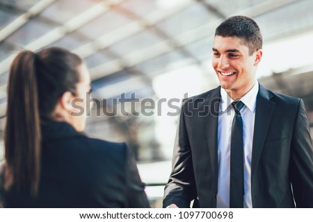 Businessman And Businesswomen Shaking Hands Outside Office #1097700698