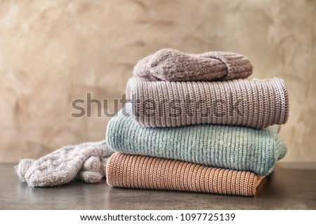 Stack of warm knitted clothes on table #1097725139