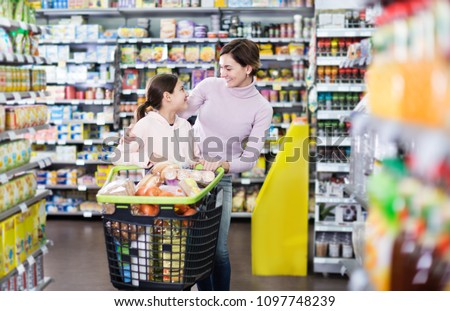 Young woman customer with girl looking for the food supplies in the supermarket. Focus on both persons  #1097748239
