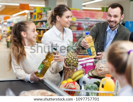 Happy family is standing with trolley with food near cashbox in the supermarket  #1097757701