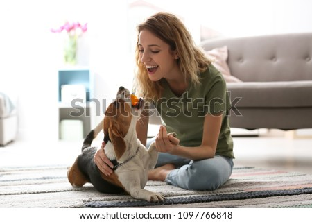 Young woman playing with her dog at home #1097766848