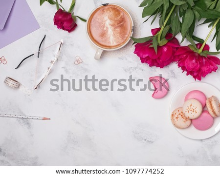 Coffee, pink peonies and macarons on the marble background, top view. #1097774252