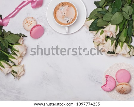 White roses, coffee and macarons on the marble background, top view #1097774255