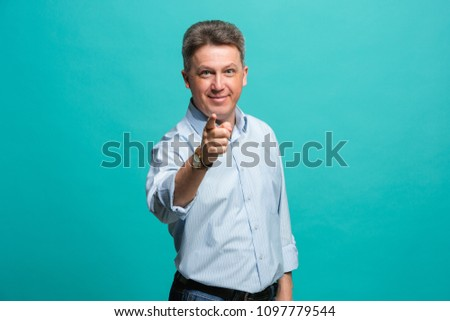I choose you and order. The smiling business man point you, want you, half length closeup portrait on blue studio background. The human emotions, facial expression concept. Front view. Trendy colors #1097779544
