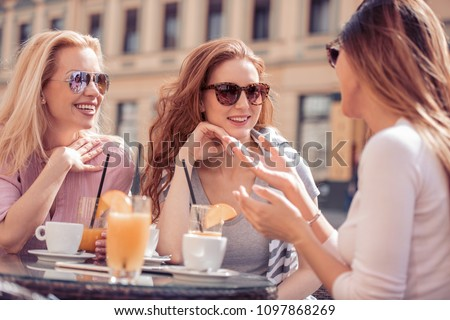 Group of friends having a coffee together. Three women at cafe, talking, laughing and enjoying their time. #1097868269