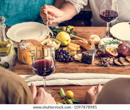 People eating a platter of cheese with seasonal fruits and wine #1097878985