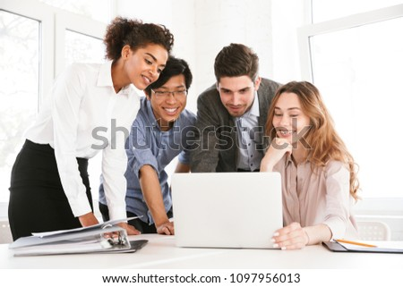 Group of smart young multiethnic businesspeople discussing ideas while looking at laptop computer Royalty-Free Stock Photo #1097956013