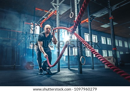 Men with battle rope battle ropes exercise in the fitness gym. CrossFit concept. gym, sport, rope, training, athlete, workout, exercises concept #1097960279