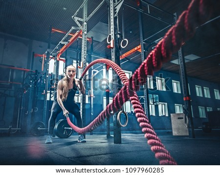 Woman with battle rope battle ropes exercise in the fitness gym. CrossFit concept. gym, sport, rope, training, athlete, workout, exercises concept #1097960285