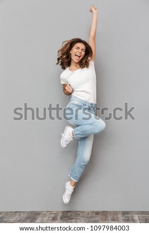 Full length portrait of a joyful young woman jumping and celebrating over gray background Royalty-Free Stock Photo #1097984003