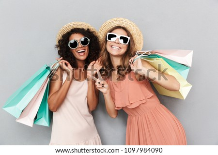 Portrait of two happy young women dressed in summer clothes holding shopping bags and showing peace gesture isolated over gray background #1097984090