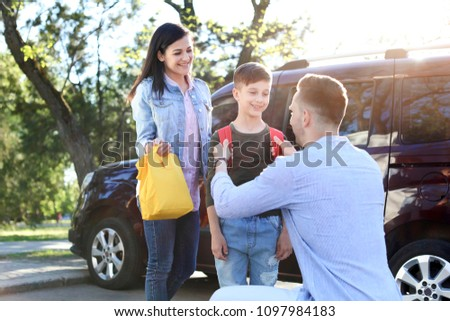 Young parents saying goodbye to their little child near school #1097984183