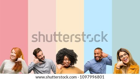Cool group of people, woman and man happy and excited making showing call me gesture with hand shaped like telephone #1097996801