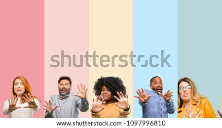 Cool group of people, woman and man disgusted and angry, keeping hands in stop gesture, as a defense, shouting #1097996810