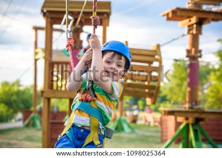 Little cute boy enjoying activity in a climbing adventure park on a summer sunny day. toddler climbing in a rope playground structure. Safe Climbing extreme sport with helmet insurance motion blurred #1098025364