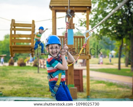 Young boy playing and having fun doing activities outdoors. Happiness and happy childhood concept. Boy swing on rope. #1098025730