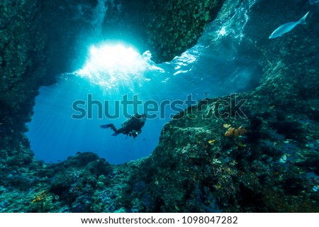 woman diver underwater at the entrance of a cave with sunrays  Royalty-Free Stock Photo #1098047282