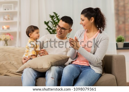family, parenthood and people concept - happy mother, father with baby daughter at home #1098079361