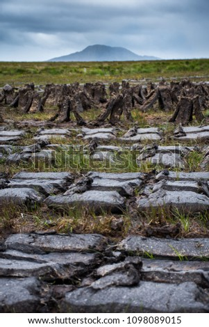 Blocks of peat cut and lefto to dry in the field on Isle of North Uist, Outer Hebrides, Scotland, with Eaval hill in the background #1098089015