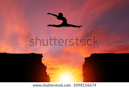 Silhouette of girl dancer in a split leap over dangerous cliffs with sunset or sunrise background and copy space. Concept of faith, conquering adversity, taking risk; challenge, courage, determination #1098156674