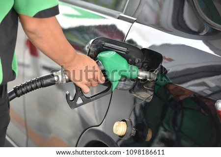 Man hand refuelling the car, Pumping gasoline fuel in car at petrol station. Royalty-Free Stock Photo #1098186611