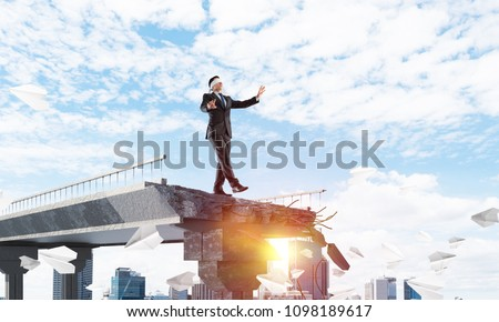 Businessman walking blindfolded among flying paper planes on concrete bridge with huge gap as symbol of hidden threats and risks. Cityscape and sunlight on background. 3D rendering. Royalty-Free Stock Photo #1098189617
