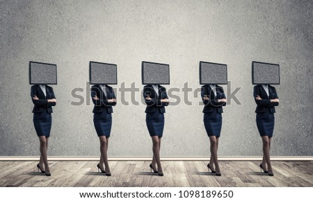 Business women in suits with TV instead of their heads keeping arms crossed while standing in a row in empty room with gray wall on background. #1098189650